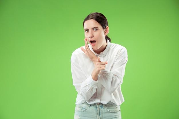 秘密のゴシップコンセプト。彼女の手の後ろに秘密をささやく若い女性。トレンディな緑のスタジオの背景に分離されたビジネス女性。若い感情的な女性。人間の感情、顔の表情の概念。