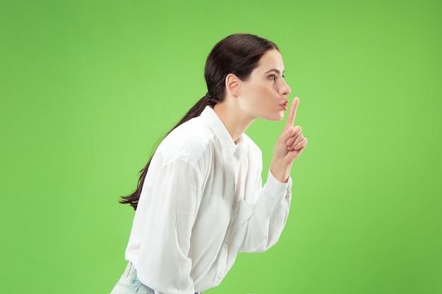 Secret, gossip concept. young woman whispering a secret behind her hand.