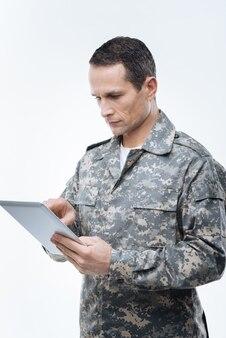 Секретная информация. серьезный позитивный умный человек, держащий планшет и использующий его во время работы с секретной военной информацией