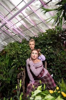 秘密の場所。彼女の友人と立っている間、茂みに隠れている美しい若い女性