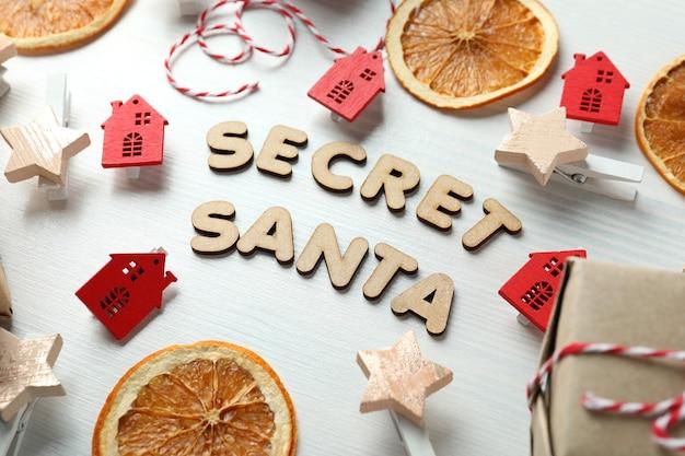 白い木製の背景に秘密のサンタとクリスマスの構成。