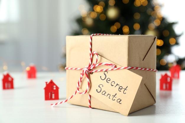 Секретный санта и рождественский состав на белом деревянном столе.