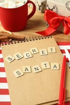 Секретный санта и рождественская композиция на деревянном столе.