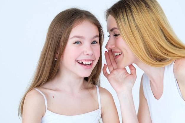 비밀 공유. 가족 신뢰 관계. 그녀의 딸 귀에 뭔가를 속삭이는 어머니.