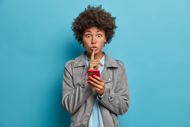 Secret surprised woman with curly hair, dark skin, makes silence gesture, holds mobile phone, creats new profile in social networks, tells secret or confidential information, poses over blue wall