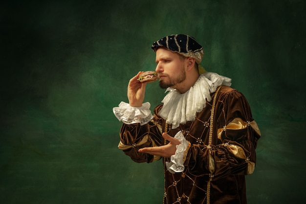 Secret taste. portrait of medieval young man in vintage clothing with wooden frame on dark background. male model as a duke, prince, royal person. concept of comparison of eras, modern, fashion.