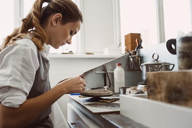 에서 새로운 은반지 작업을 하는 젊은 여성 보석상의 비밀 기술 측면