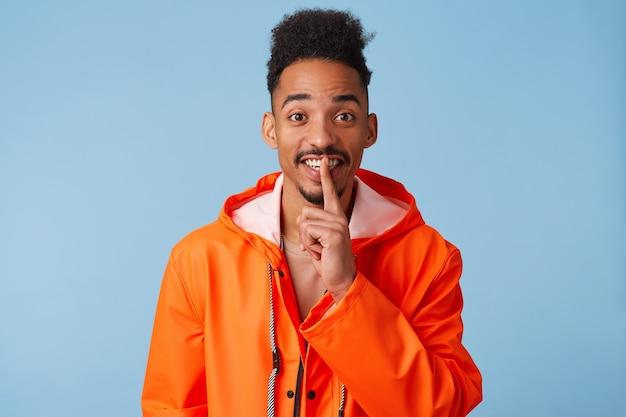 Il giovane ragazzo dalla pelle scura afroamericano segreto indossa un impermeabile arancione ha un'espressione misteriosa, tocca le labbra con l'indice, sorride ampiamente e si alza.