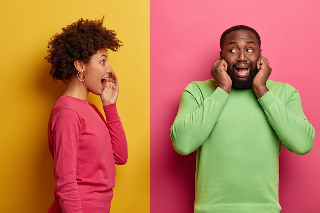 Secret young woman stands in profile, whispers secret to boyfriend who doesnt want to hear her, plugs ears, avoids gossiping. funny afro american woman tells secret information, poses sideways