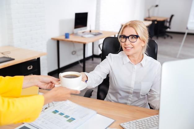 秘書がオフィスで笑顔の上司のためにコーヒーを持ってきます