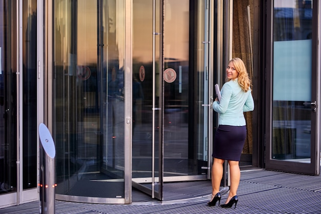 Секретарь в деловом костюме стоит возле вращающейся двери