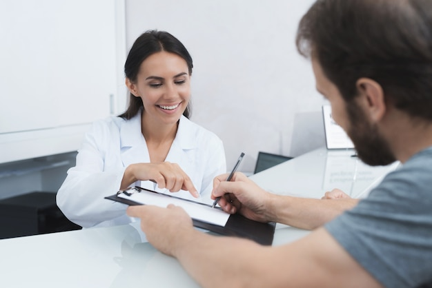 The secretary in a medical clinic helps the patient.