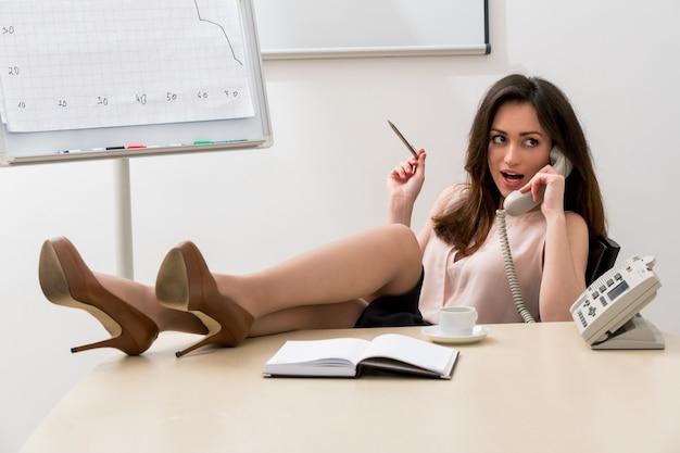 비서는 직장에서 테이블 점원에 그녀의 다리와 전화 비즈니스 여자에 말한다