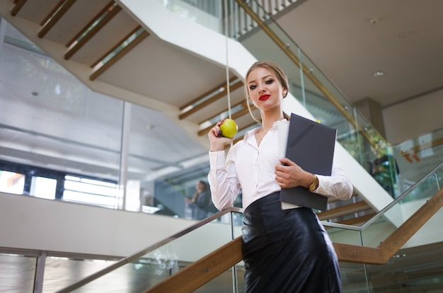Secretary with papers and an apple in her hands goes for lunch on the stairs in the office. business woman concept