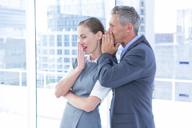 Secretive business colleagues whispering