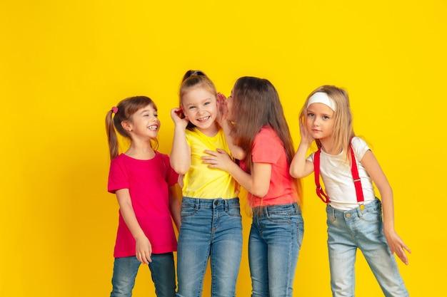 秘密。黄色のスタジオの背景で一緒に遊んで楽しんで幸せな子供たち。明るい服を着た白人の子供たちは、遊び心があり、笑い、笑顔に見えます。教育、子供時代、感情の概念。