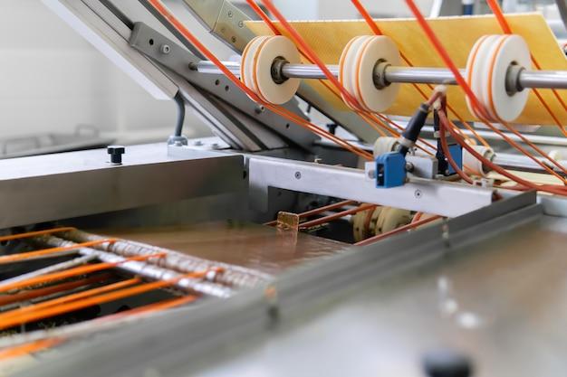 チョコレートを充填した多層ウェーハを製造するための機械のコンベヤーのセクション