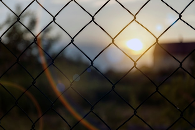 Secure fence at sunset with bokeh.