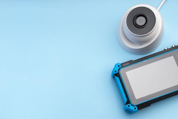 Монитор камеры видеонаблюдения и тестера видеонаблюдения на синем фоне с пространством для текста