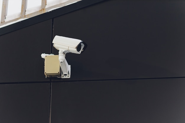 Security camera on dark modern building, technology concept.