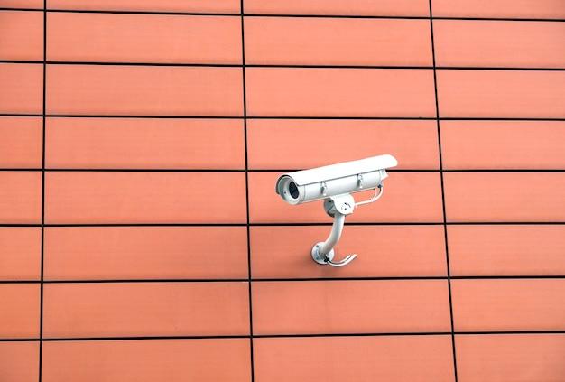 Камера видеонаблюдения установлена на оранжевой стене современного здания, горизонтальный вид крупным планом