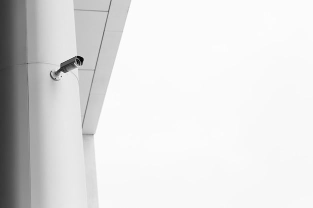 Камера видеонаблюдения на светлом современном здании, технологическая концепция. копировать пространство