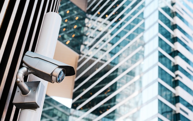 Security camera on the street on modern office buildings background