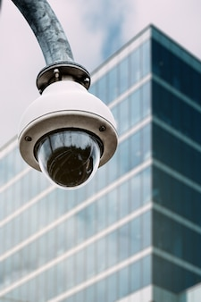 Security camera with a glass building on the background