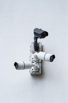 Камеры видеонаблюдения на белом современном здании, технологическая концепция