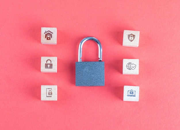 Security concept with lock, icons on wooden cubes on pink table flat lay.