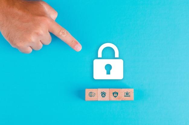 Concetto di sicurezza con blocchi di legno, icona del lucchetto di carta sul piatto blu laici. puntamento della mano dell'uomo.