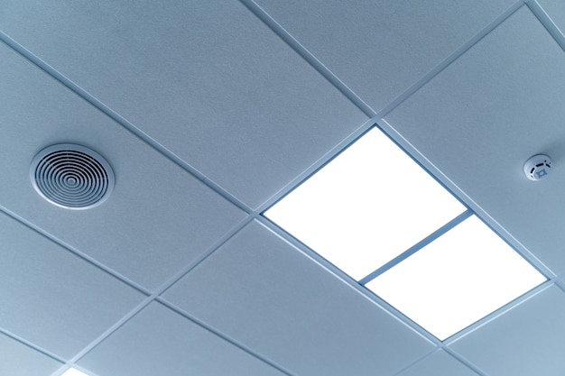 Security and fire alarm on the ceiling in administrative building. square lamps built inside the ceiling.