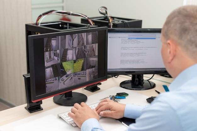 Охранник наблюдает за камерами видеонаблюдения в комнате безопасности контроль видеонаблюдения