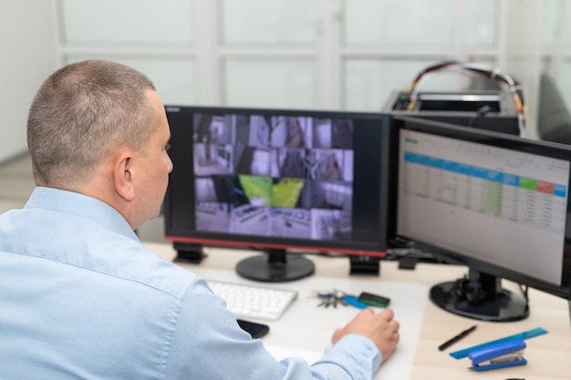 보안실에서 cctv 카메라를 모니터링하는 경비원