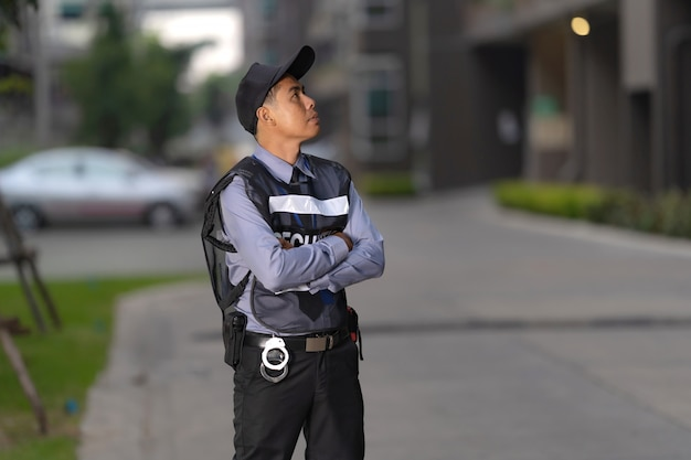 Security man standing outdoors near big building