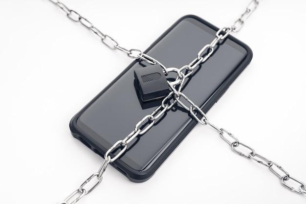 Безопасность на смартфоне, цепи и замке на смартфоне. кибербезопасность на концепции цифровых устройств