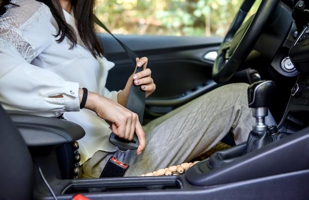 도로 보안. 자동차 안에 앉아 안전 벨트를 고정하는 여성 드라이버