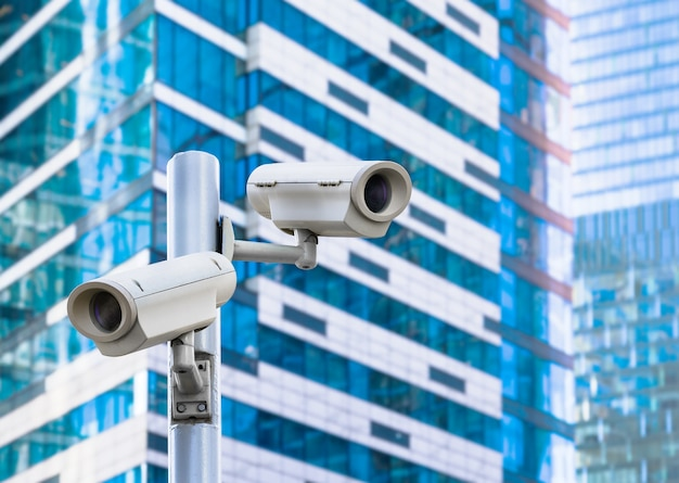 Security street cameras on blue modern office buildings background