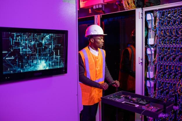 보안 시스템 엔지니어가 서버 구성 요소와 함께 카트를 밀고 있습니다.
