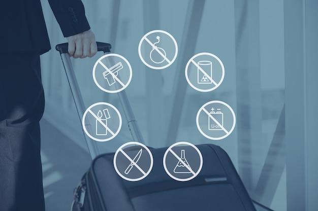 セキュリティ警告。空港でスーツケースを引っ張るビジネスマンの写真の上に設定されたデジタル構成のアイコン