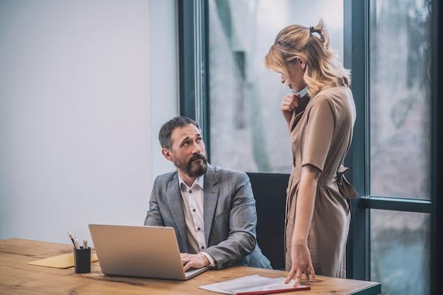 上司を誘惑します。オフィスのテーブルに座っている驚いた大人の上司の前に立っているドレスを着たかなり金髪の若い女性