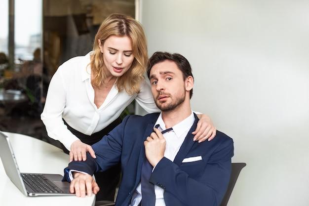 Соблазнение подчиненного в офисе. кавказская блондинка трогает коллегу-мужчину, который сидит за столом