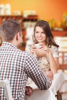 Seducing beautiful woman looking at her lover with coffee cup. having romantic talk