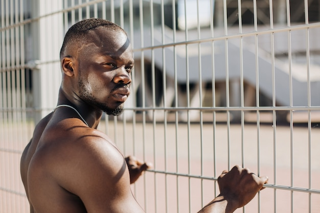 Seductive african american man with muscels poses with naked chest before the fence