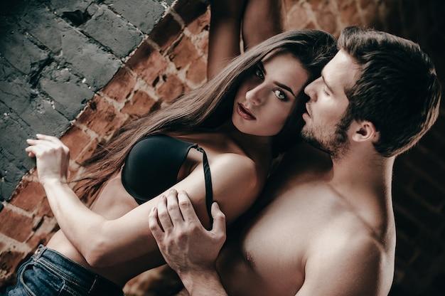 매혹적이고 아름답습니다. 잘생긴 젊은 벗은 남자가 벽돌 벽 근처에 서 있는 동안 아름다운 여자 친구의 브래지어 끈을 당기고 있습니다.