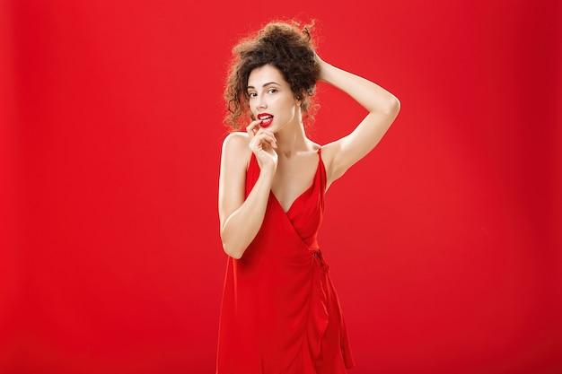빨간 이브닝 드레스를 입고 고급스러운 헤어스타일로 머리를 빗고 있는 매혹적이고 관능적인 우아한 부유한 여성...