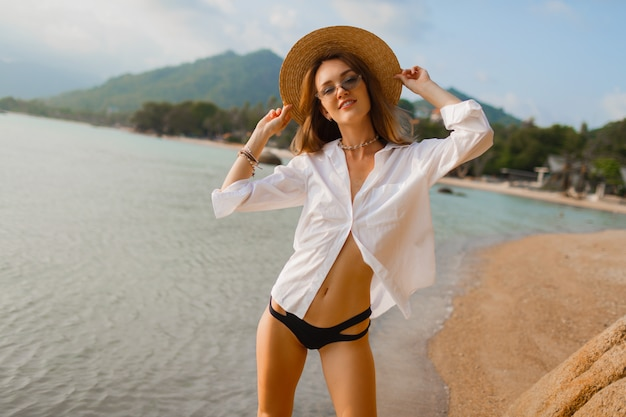 熱帯のビーチでポーズ白いブラウスで魅惑的な金髪の女性
