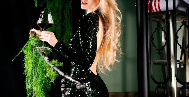 Соблазнительная блондинка в зеленом вечернем платье позирует с бокалом красного вина. смешанная техника
