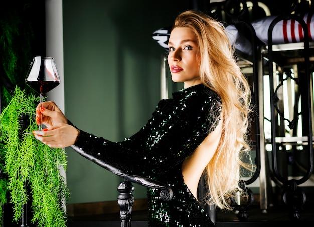 赤ワインのグラスでポーズをとる緑のイブニングドレスの魅惑的なブロンド。