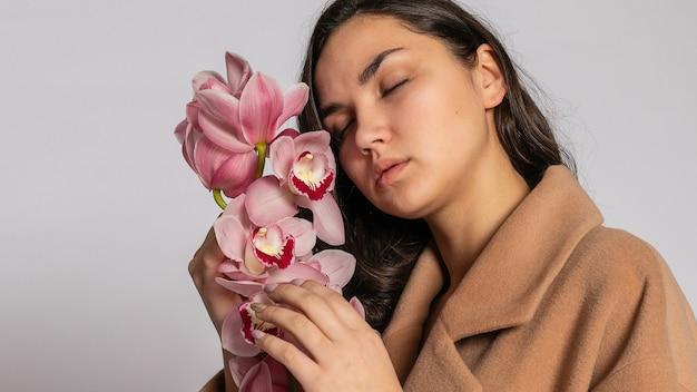 파스텔 캐주얼 봄 복장에 회색 background.elegant 모델에 스튜디오에서 포즈 갈색 재킷에 매혹적인 금발 여자. 건강한 피부와 난초를 가진 아름다운 소녀. 16:9 파노라마 형식.